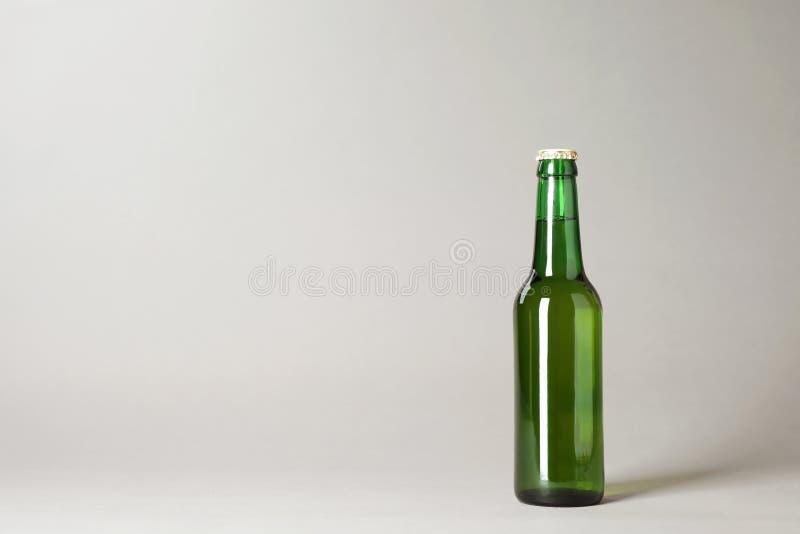 Botella de cerveza en fondo gris imágenes de archivo libres de regalías