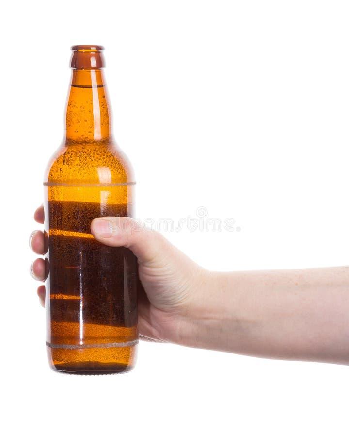 Botella de cerveza en la mano imagenes de archivo