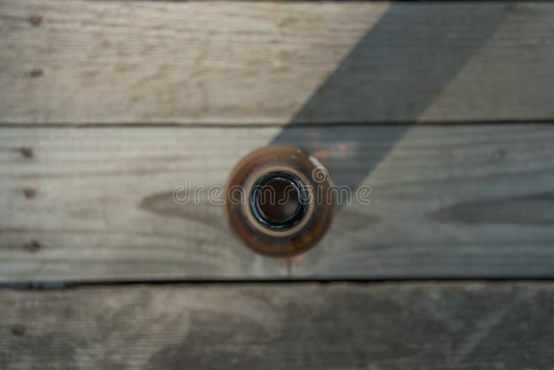 Botella de cerveza en un fondo de madera imagenes de archivo