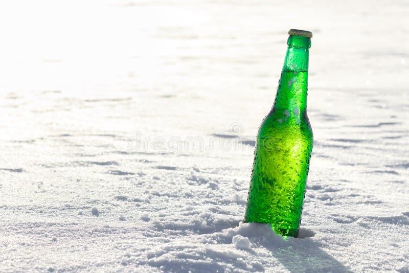 Botella de cerveza fría en la nieve imágenes de archivo libres de regalías