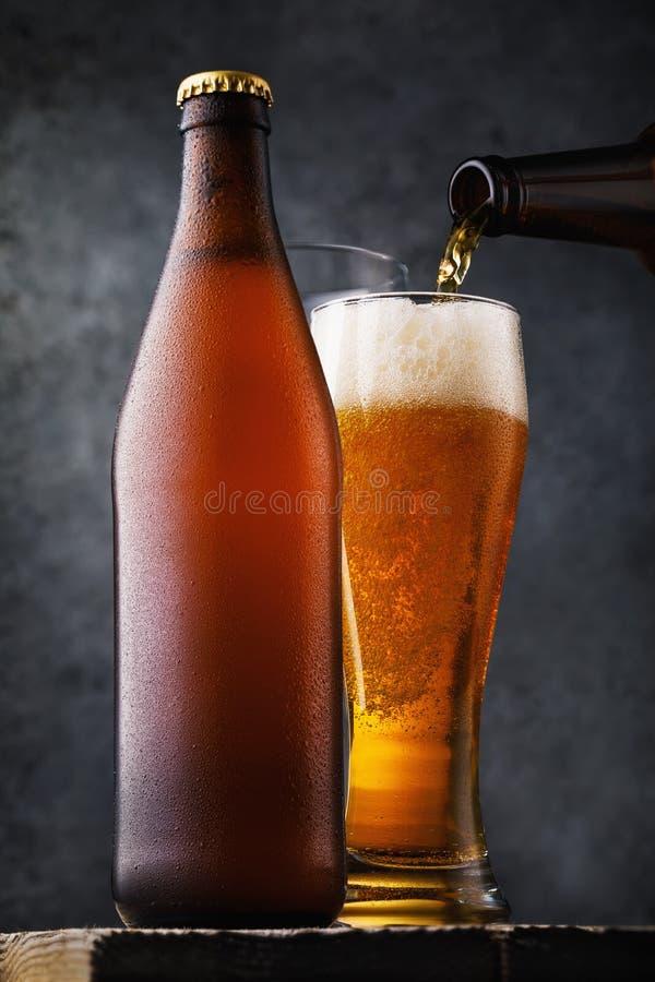 Botella de cerveza ligera y de un vidrio lleno de la bebida en una tabla de madera Vida inmóvil alcohólica imágenes de archivo libres de regalías