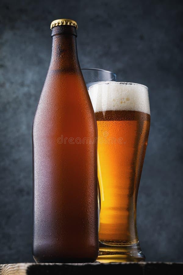 Botella de cerveza ligera y de un vidrio lleno de la bebida fría en una tabla de madera fotos de archivo libres de regalías
