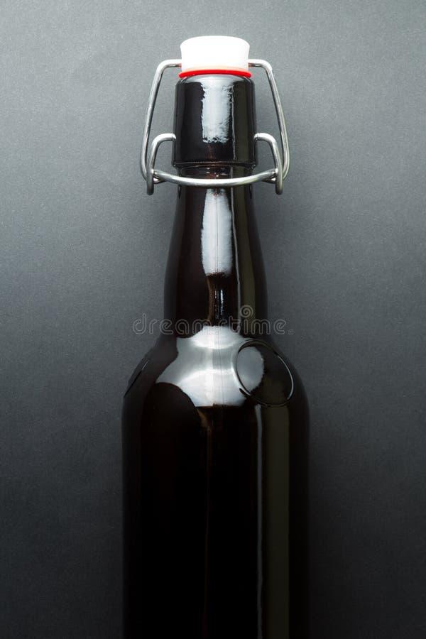 Botella de cerveza marr?n del vintage aislada en un fondo negro vertical fotos de archivo