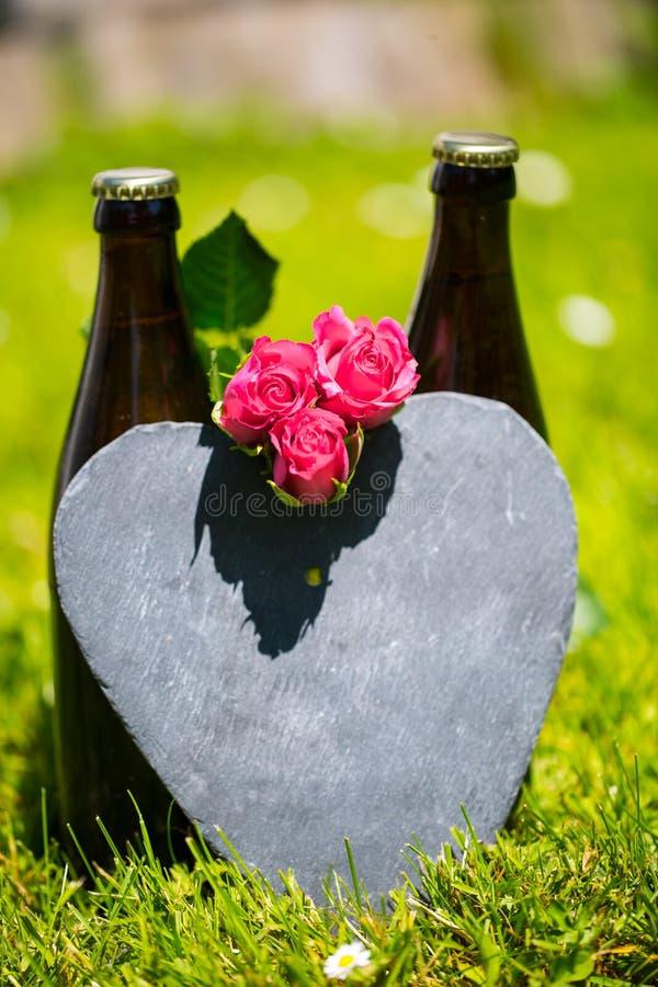 Botella de cerveza que miente con las rosas para el día de padre foto de archivo