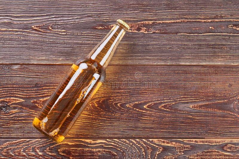 Botella de cerveza que miente en la tabla de madera imagenes de archivo
