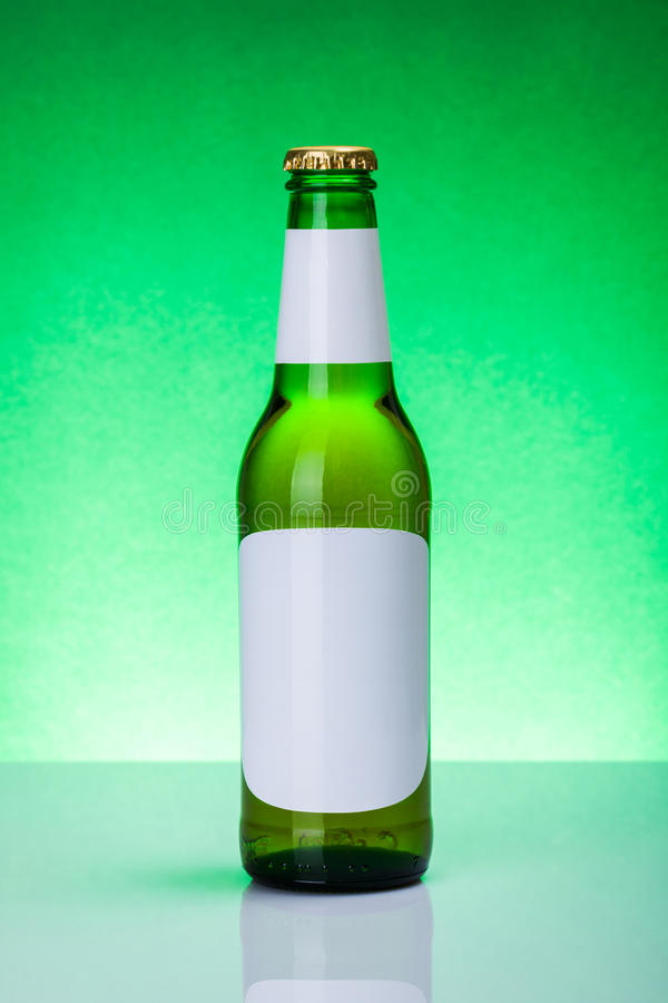Botella de cerveza verde con las etiquetas en blanco fotos de archivo