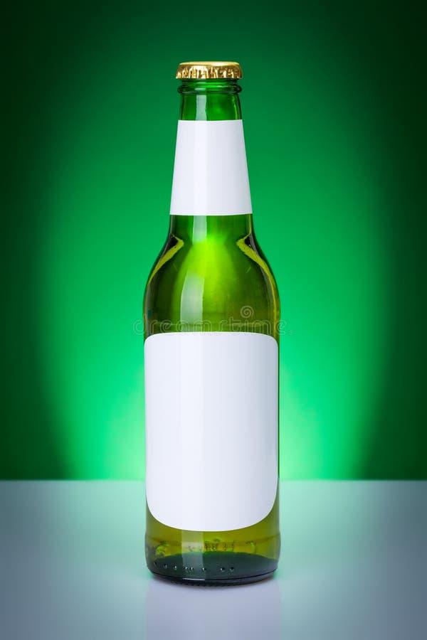 Botella de cerveza verde con las etiquetas en blanco imágenes de archivo libres de regalías