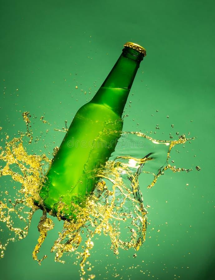 Botella de cerveza verde con salpicar el líquido fotos de archivo