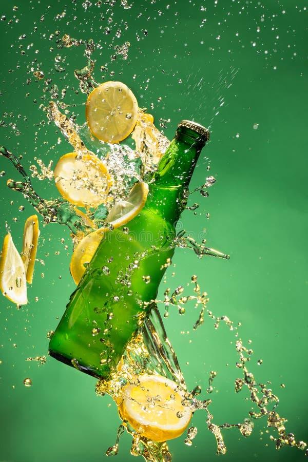 Botella de cerveza verde con salpicar el líquido fotos de archivo libres de regalías