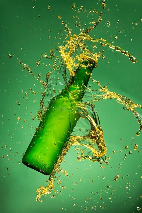 Botella de cerveza verde con salpicar el líquido imagen de archivo libre de regalías