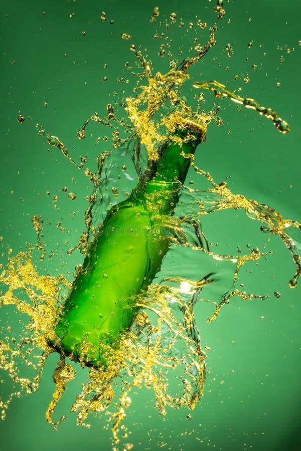 Botella de cerveza verde con salpicar el líquido imágenes de archivo libres de regalías