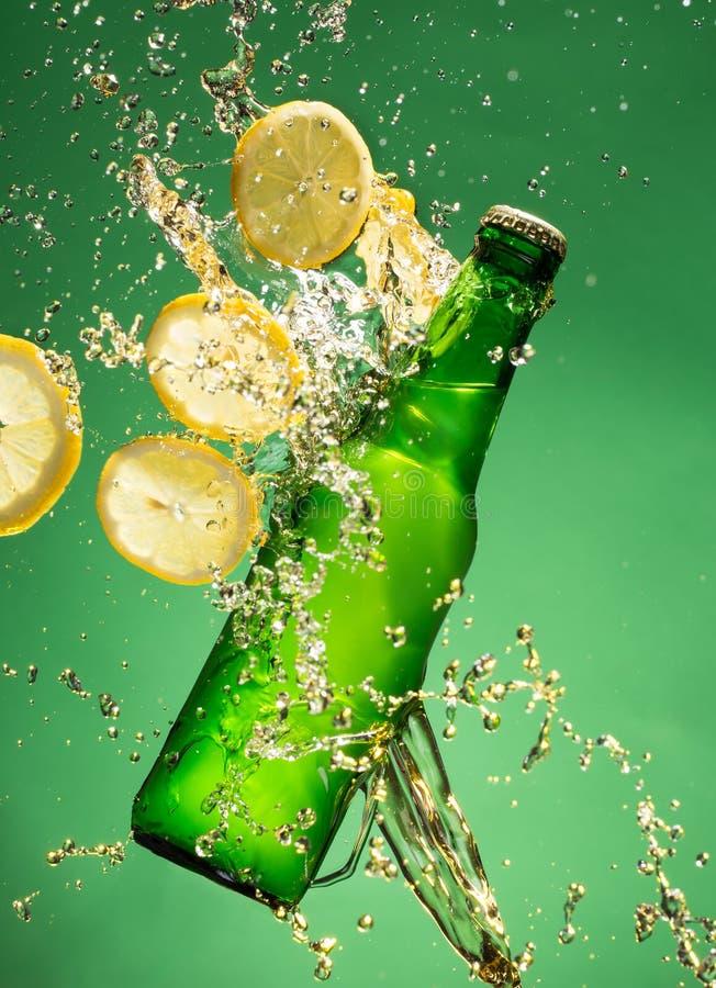 Botella de cerveza verde con salpicar el líquido foto de archivo libre de regalías