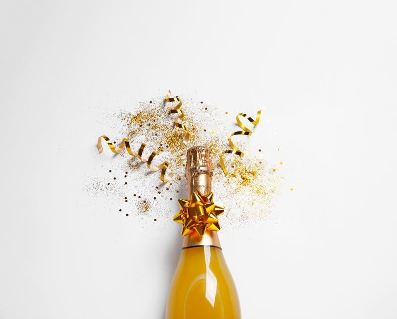 Botella de champán con brillo del oro y de arco en el fondo blanco, visión superior hilarante imagen de archivo libre de regalías