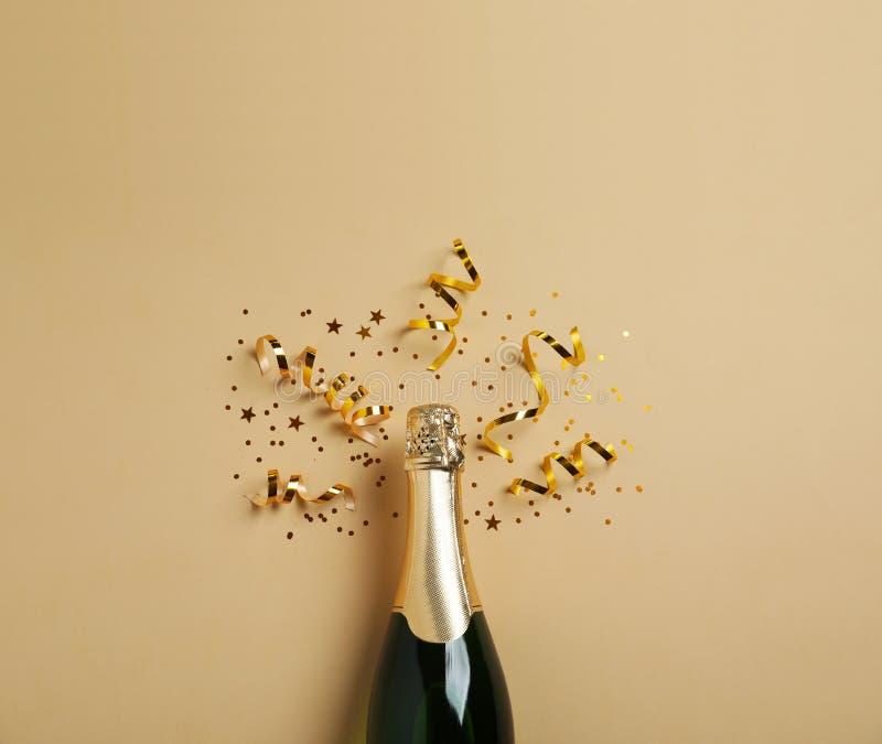 Botella de champán con brillo del oro y de confeti en el fondo beige, endecha plana hilarante fotos de archivo
