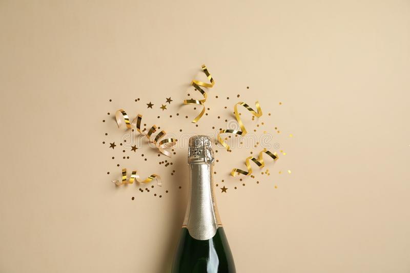 Botella de champán con brillo del oro y de confeti en fondo beige Celebración hilarante foto de archivo libre de regalías
