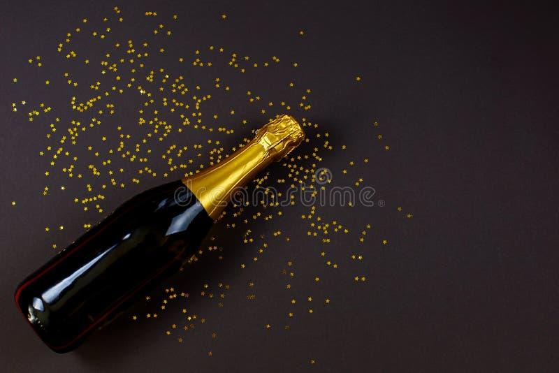Botella de champán con confeti estrella sobre fondo negro fotos de archivo libres de regalías