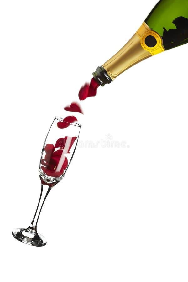 Botella de champán que vierte los pétalos color de rosa rojos en el vidrio imágenes de archivo libres de regalías