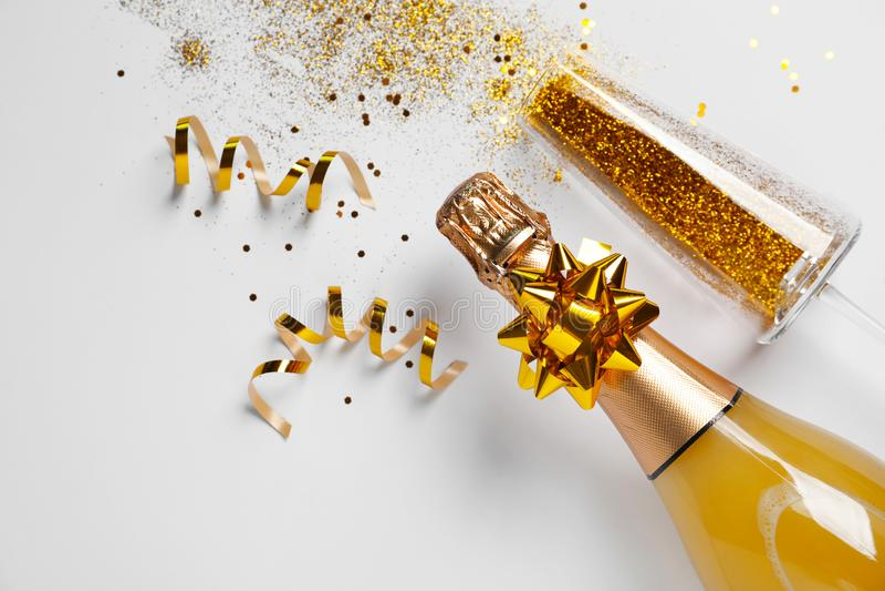Botella de champán y de vidrio con brillo del oro en el fondo blanco, visión superior hilarante foto de archivo libre de regalías