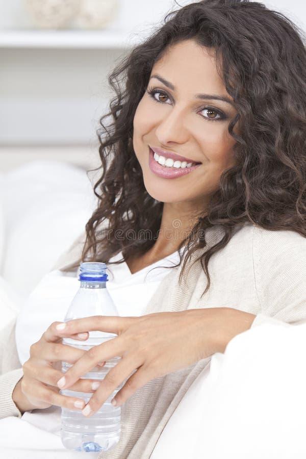 Botella de consumición de la mujer hispánica feliz de agua fotos de archivo libres de regalías