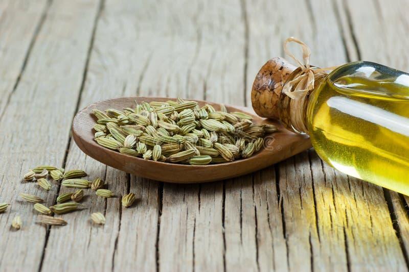 Botella de cristal de aceite esencial del hinojo con las semillas de hinojo en cuchara de madera en la tabla de madera fotos de archivo