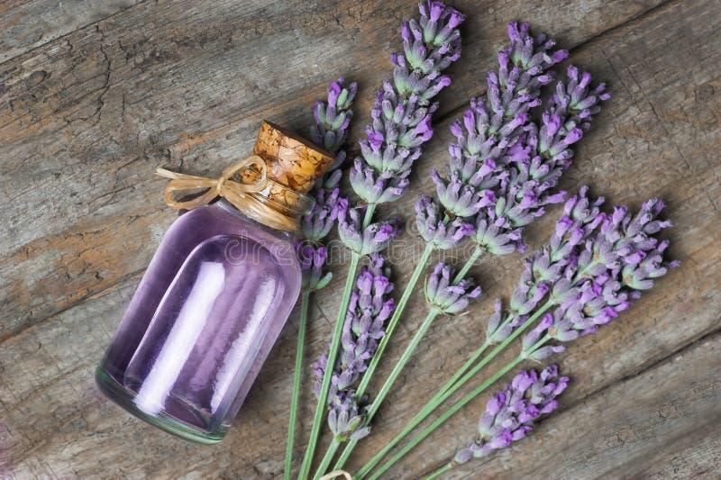 Botella de cristal de aceite esencial de la lavanda con las flores frescas de la lavanda en la tabla rústica de madera foto de archivo