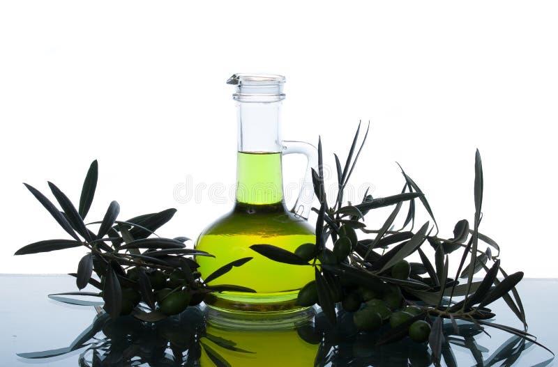 Botella de cristal con aceite y ramas de olivo virginales adicionales de oliva Brunch del olivo con las aceitunas fotos de archivo