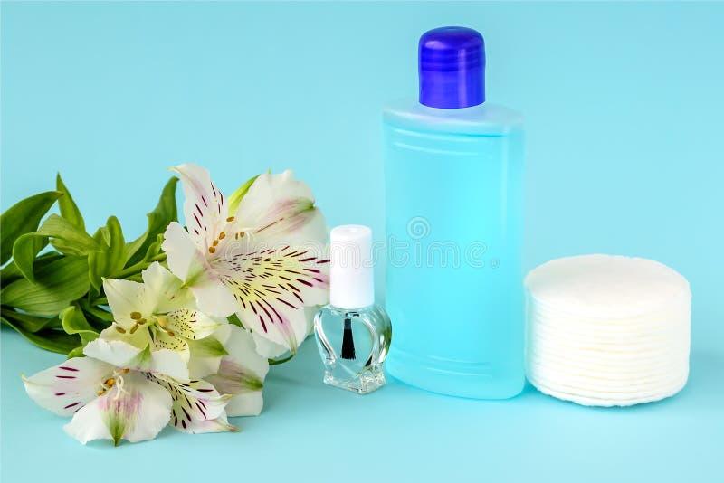 Botella de cristal con el esmalte de uñas descolorido, botella plástica con el removedor de barniz de clavo, cojines de algodón y imagen de archivo libre de regalías