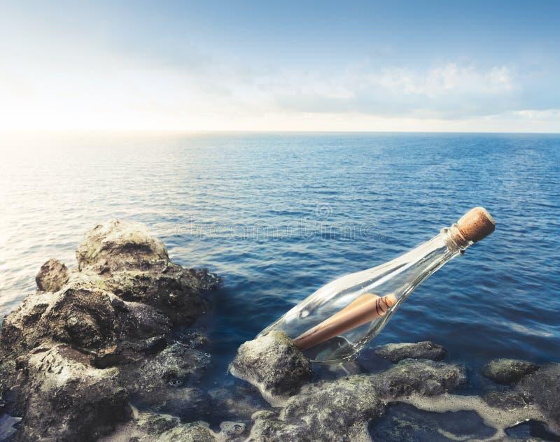 Botella de cristal con el mensaje en el mar fotos de archivo