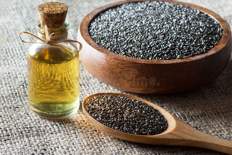 Botella de cristal del aceite y de las semillas Salvia Hispanica del chia de Chia en cuchara y cuenco de madera en el contexto de foto de archivo