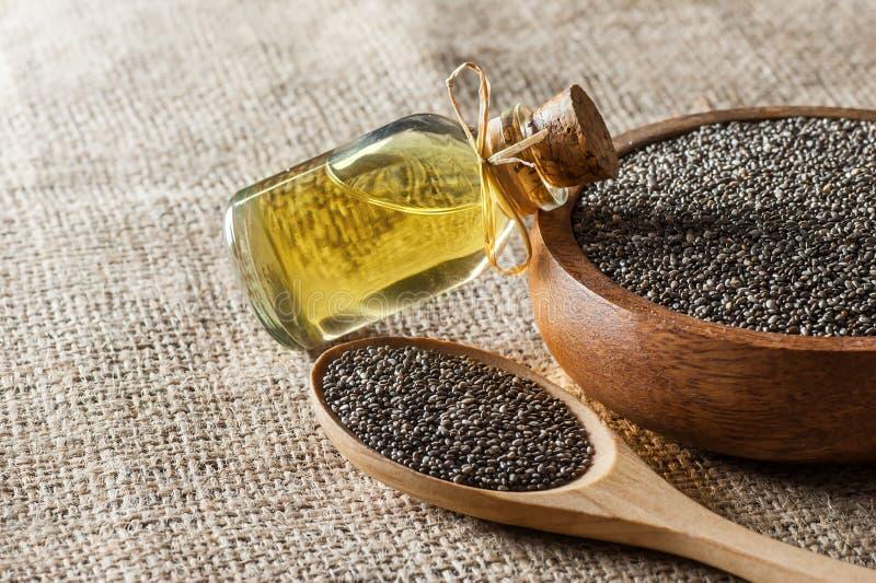 Botella de cristal del aceite y de las semillas Salvia Hispanica del chia de Chia en cuchara y cuenco de madera en el contexto de fotografía de archivo libre de regalías