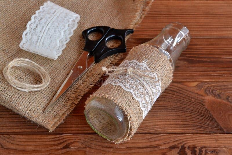 Botella de cristal diy hecha en casa Tijeras, arpillera, florero hecho a mano en una tabla de madera Estilo rústico Concepto fáci imagen de archivo libre de regalías