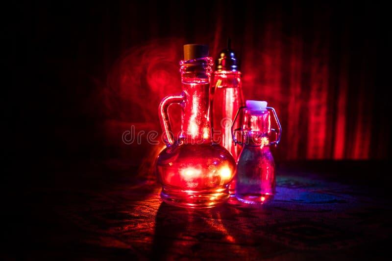 Botella de cristal de la antigüedad y del vintage en fondo de niebla oscuro con la luz Veneno o concepto del líquido de la magia imagen de archivo
