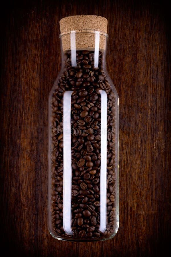 Botella de cristal por completo de granos de café imagen de archivo
