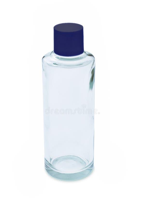 Botella de cristal vacía con el casquillo azul imagenes de archivo
