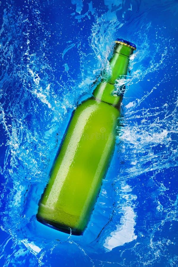 Botella de cristal verde en agua foto de archivo