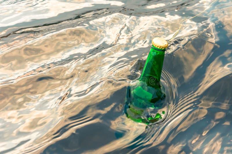 Botella de cristal verde en el mar con un mensaje imagen de archivo