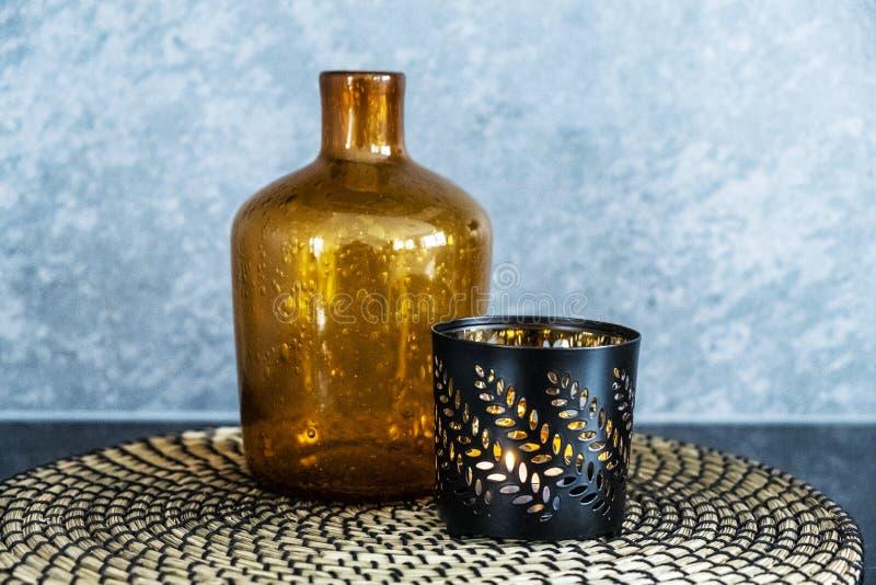 Botella de cristal y palmatoria decorativas con la luz imagenes de archivo