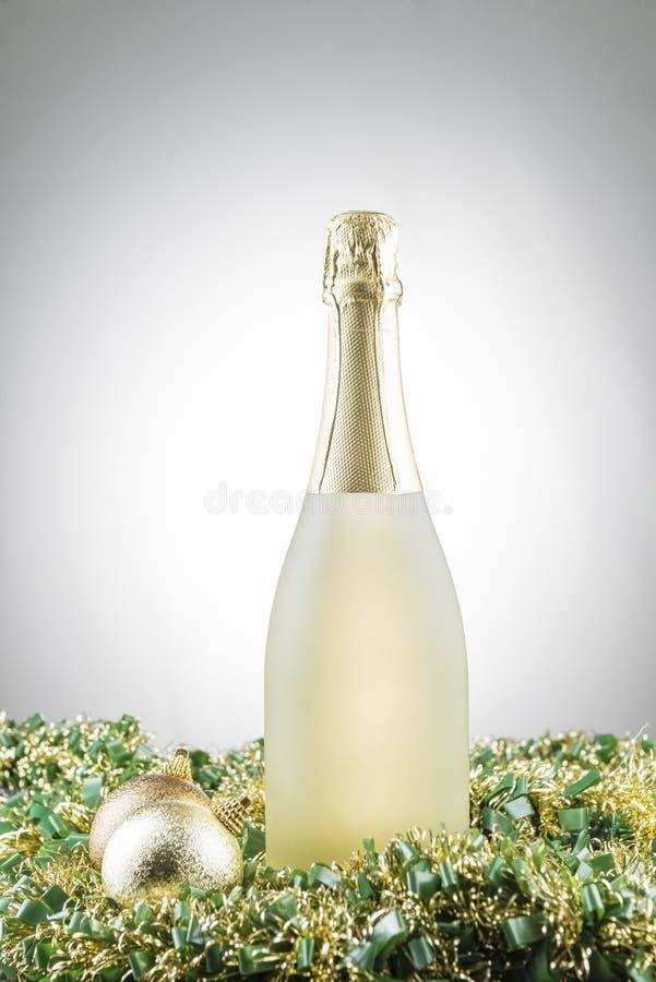 Botella de decoraciones del champán y de la Navidad en las guirnaldas con el fondo blanco de la pendiente foto de archivo