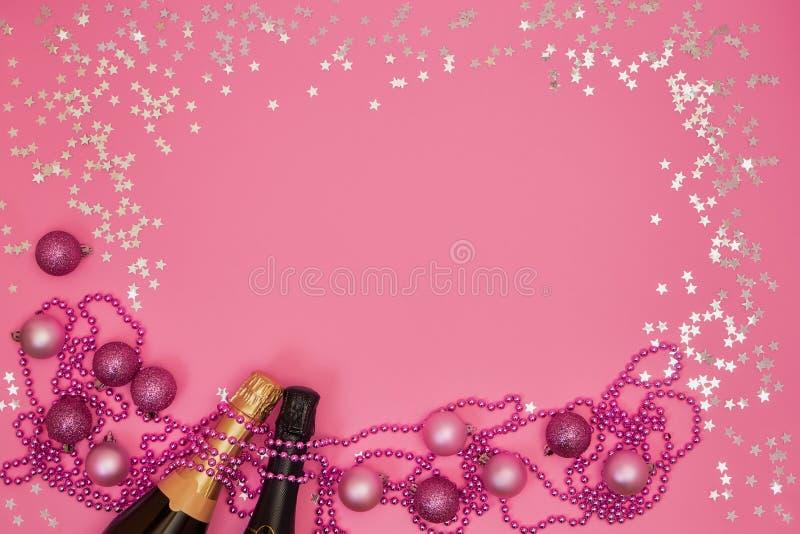 Botella de dos Champán con los ornamentos de la Navidad en fondo rosado imágenes de archivo libres de regalías