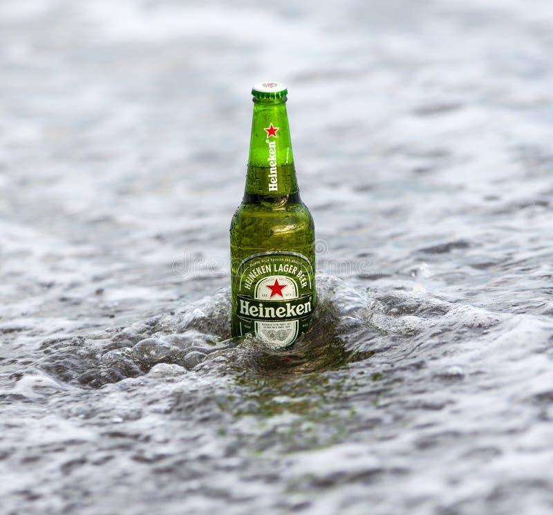 Botella de Heineken Lager Beer en el océano Heineken Lager Beer es una cerveza de cerveza dorada pálida producida por la compañía fotos de archivo libres de regalías