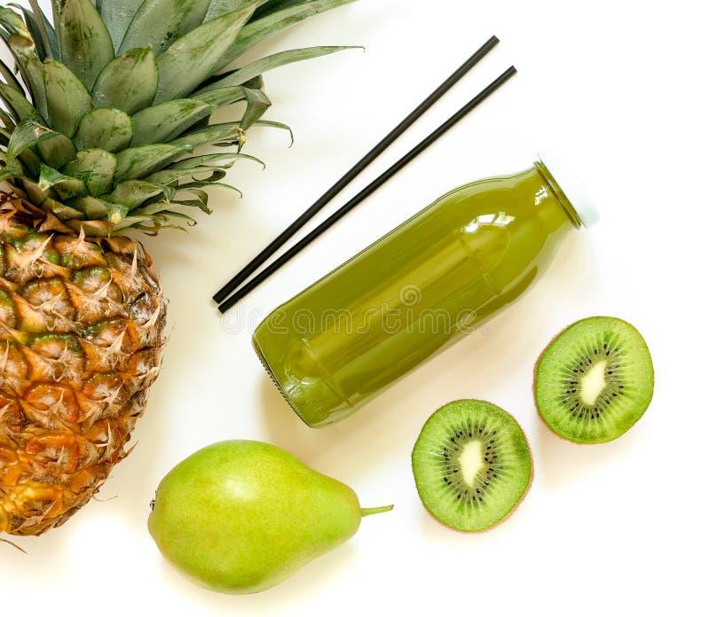 Botella de kiwi, de piña, de jugo de la pera aislado en blanco y de ingredientes imagen de archivo