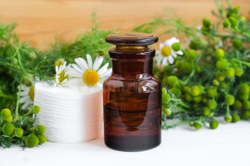 Botella de la farmacia con el cosmético/el aceite de limpiamiento/curativo del aroma de la manzanilla salvaje o el tinte y cojine imágenes de archivo libres de regalías