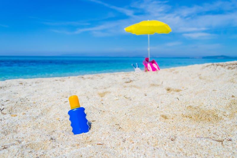 Botella de la loción y parasol de playa en la arena imagen de archivo