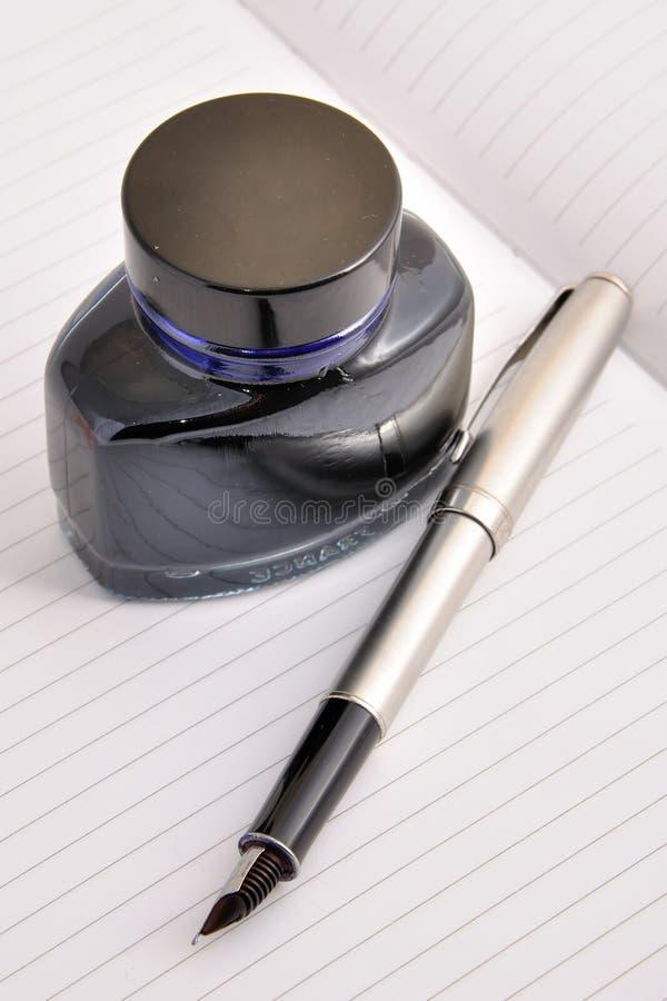 Botella de la pluma y de tinta que miente en una hoja limpia foto de archivo