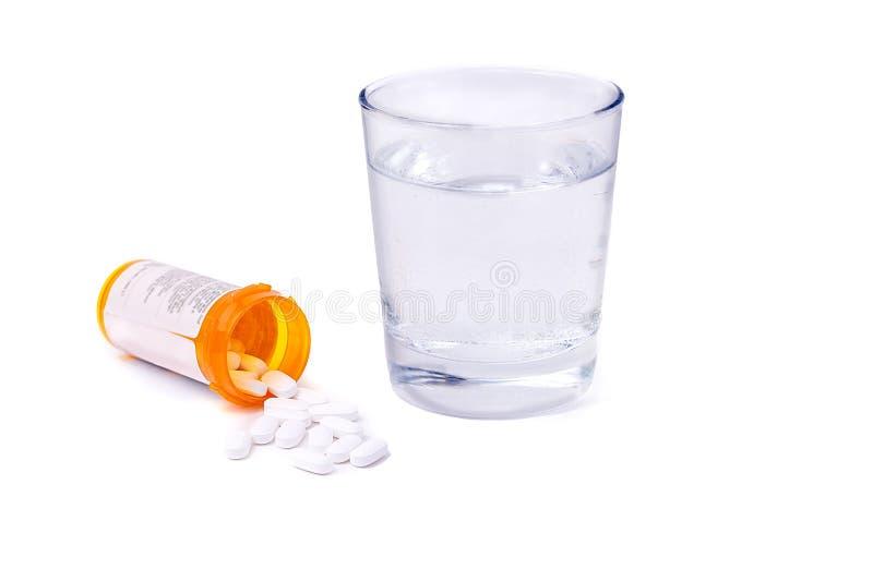 Botella de la prescripción y píldoras y vaso de agua aislados fotografía de archivo
