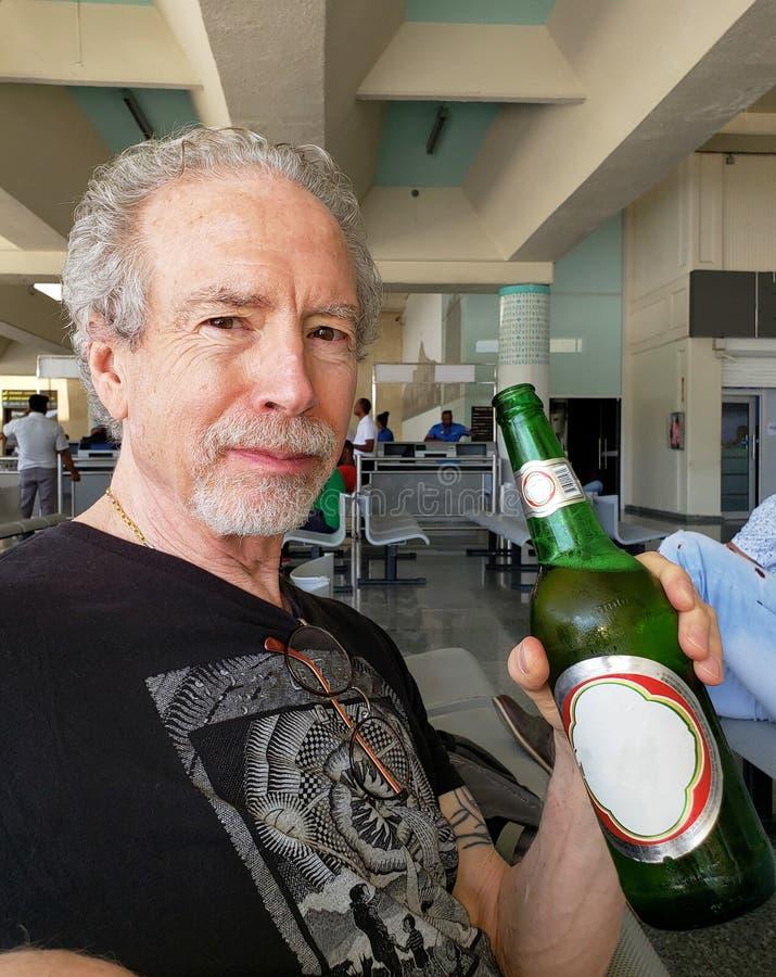 Botella de la tenencia de un más viejo hombre de cerveza en zona de espera del aeropuerto fotos de archivo libres de regalías
