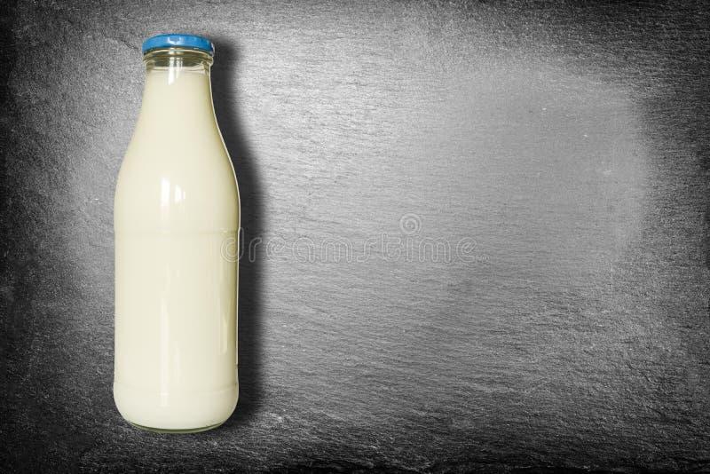 Botella de leche con la tapa azul aislada en la pizarra oscura - cerrada fotografía de archivo