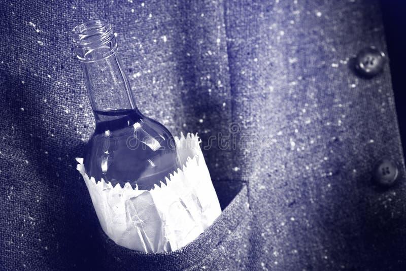 Botella de licor duro en el bolsillo fotografía de archivo