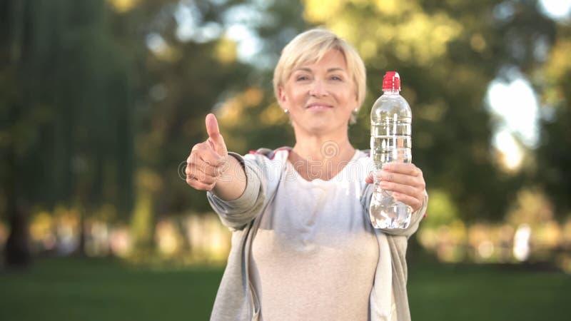 Botella de mediana edad de la demostración de la mujer de agua y de pulgares para arriba, forma de vida sana foto de archivo libre de regalías