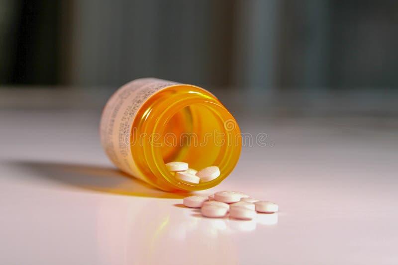 Botella de medicación de la prescripción con algunas tabletas que se derraman hacia fuera con un fondo suave fotografía de archivo libre de regalías